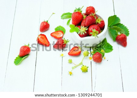 fresh ripe and under ripe strawberry fruits, flowers, leaves on white wood table background #1309244701