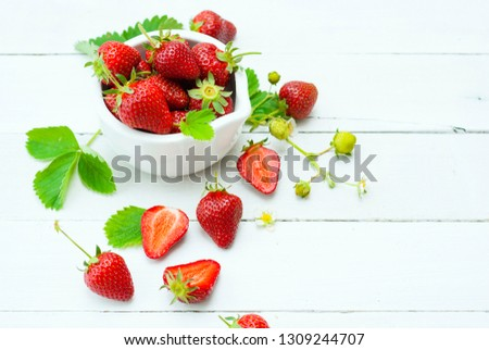 fresh ripe and under ripe strawberry fruits, flowers, leaves on white wood table background #1309244707