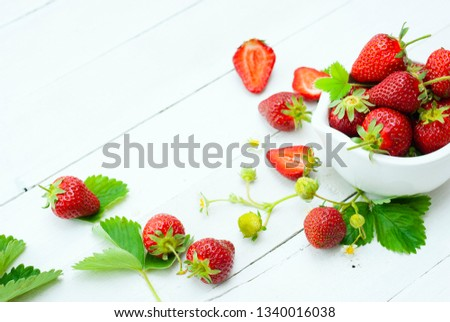 fresh ripe and under ripe strawberry fruits, flowers, leaves on white wood table background #1340016038