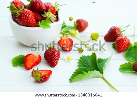 fresh ripe and under ripe strawberry fruits, flowers, leaves on white wood table background #1340016041