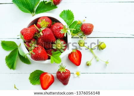 fresh ripe and under ripe strawberry fruits, flowers, leaves on white wood table background #1376056148