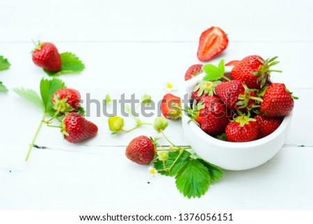 fresh ripe and under ripe strawberry fruits, flowers, leaves on white wood table background #1376056151