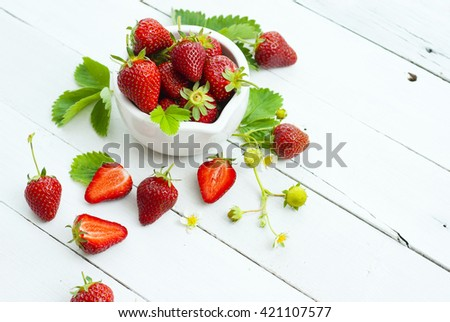 fresh ripe and under ripe strawberry fruits, flowers, leaves on white wood table background #421107577