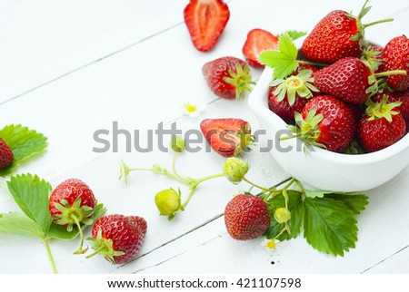 fresh ripe and under ripe strawberry fruits, flowers, leaves on white wood table background #421107598