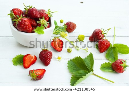 fresh ripe and under ripe strawberry fruits, flowers, leaves on white wood table background #421108345