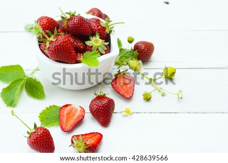 fresh ripe and under ripe strawberry fruits, flowers, leaves on white wood table background #428639566