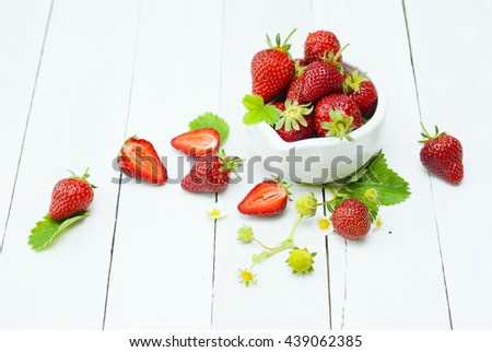 fresh ripe and under ripe strawberry fruits, flowers, leaves on white wood table background #439062385