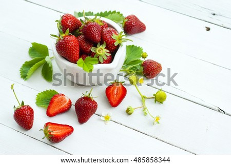 fresh ripe and under ripe strawberry fruits, flowers, leaves on white wood table background #485858344
