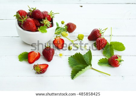 fresh ripe and under ripe strawberry fruits, flowers, leaves on white wood table background #485858425