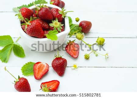fresh ripe and under ripe strawberry fruits, flowers, leaves on white wood table background #515802781