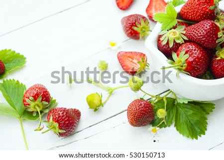 fresh ripe and under ripe strawberry fruits, flowers, leaves on white wood table background #530150713