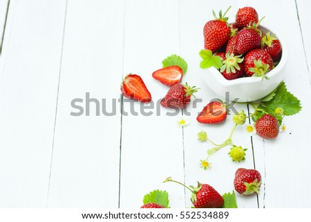 fresh ripe and under ripe strawberry fruits, flowers, leaves on white wood table background #552534889