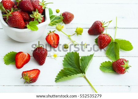 fresh ripe and under ripe strawberry fruits, flowers, leaves on white wood table background #552535279