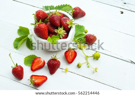 fresh ripe and under ripe strawberry fruits, flowers, leaves on white wood table background #562214446