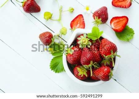 fresh ripe and under ripe strawberry fruits, flowers, leaves on white wood table background #592491299