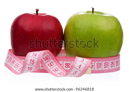 Fresh ripe apples with a measure tape wrapped around on a white background - stock photo