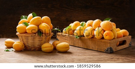 fresh ripe apricots in a basket on a wooden table Сток-фото ©