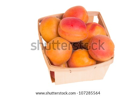 Fresh ripe apricots in wooden basket isolated on white