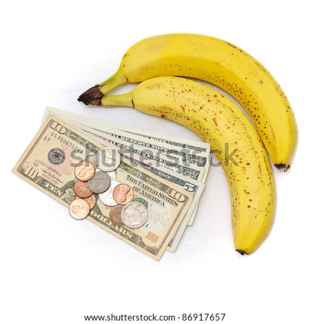 Fresh ripe bananas on white with US currency, dollars and coins, as a concept for the rising cost of commodities, inflation, rising food costs, hunger. - stock photo
