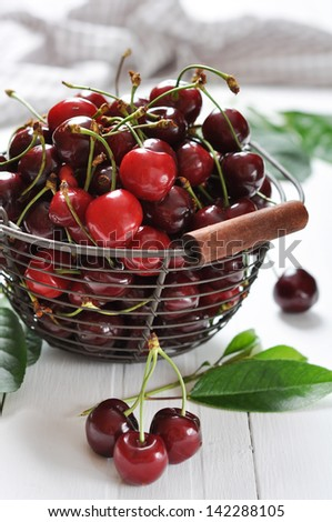 Fresh ripe cherries in a metal basket on wooden background