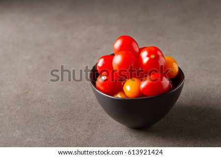 Fresh ripe cherry tomatoes in a ceramic bowl. Dark gray background #613921424