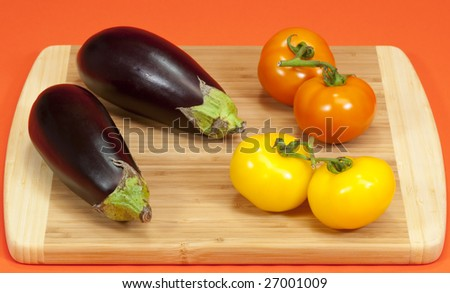 Fresh ripe eggplant and vine ripe tomatoes on a wooden cutting board