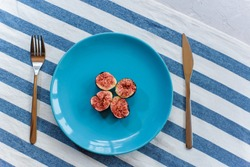 Fresh, ripe figs on a blue plate, which stands on a table covered with a striped napkin