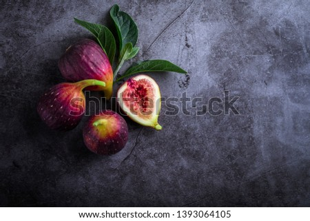 Fresh ripe figs with green leaf and on dark table black background. Healthy Mediterranean fig fruit. Beautiful blue-violet figs with empty copy space close up. Stockfoto ©