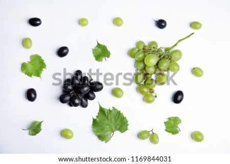 Fresh ripe juicy grapes and leaves on white background, top view