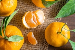 Fresh ripe juicy yellow mandarin ( clementine, tangerine ) on rustic vintage table with leaf. Winter fruit background concept