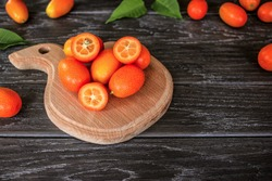 fresh ripe kumquat close-up. kumquat on a wooden background. ripe kumquat on a chopping Board. background with kumquat.