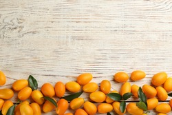 Fresh ripe kumquats on white wooden table, flat lay. Space for text