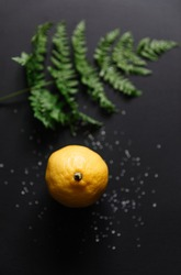 Fresh ripe lemon and grean leaves on Dark vintage wood texture background.