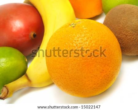 Fresh ripe limes, kiwis, mango, banana and oranges placed on a white table