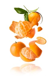 Fresh ripe mandarine with leaves falling in the air. Cut and whole mandarine isolated on white background. Food levitation concept. High resolution image