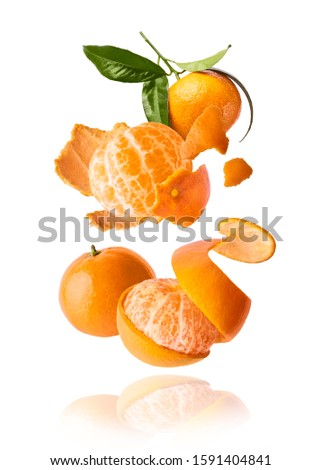 Fresh ripe mandarine with leaves falling in the air. Cut and whole mandarine isolated on white background. Food levitation concept. High resolution image ストックフォト ©
