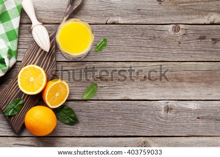 Fresh ripe oranges and juice on wooden table. Top view with copy space