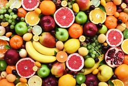 Fresh ripe organic fruits from market: apple and orange, grapefruit and banana, grape and apricot; healthy fruit background