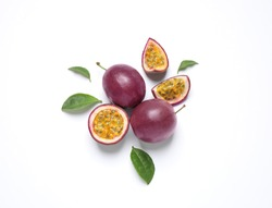 Fresh ripe passion fruits (maracuyas) with leaves on white background, flat lay