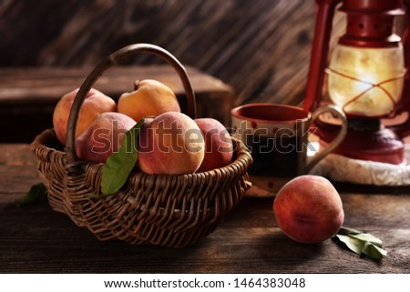 fresh ripe peaches in a wicker basket on rustic style wooden table