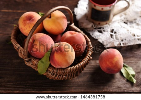 fresh ripe peaches in a wicker basket on rustic style wooden table-top view