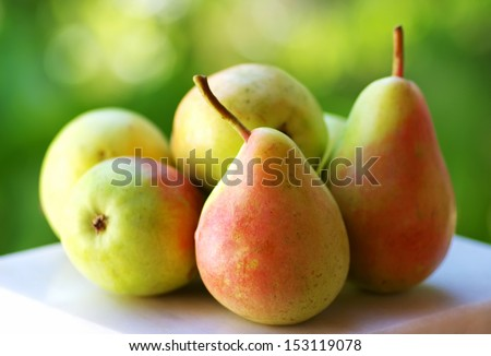 Fresh ripe pears on green background