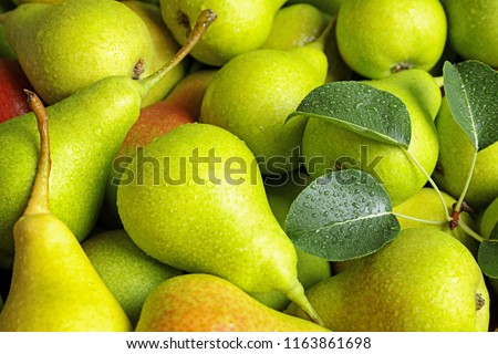 Fresh ripe pears with leaves as background