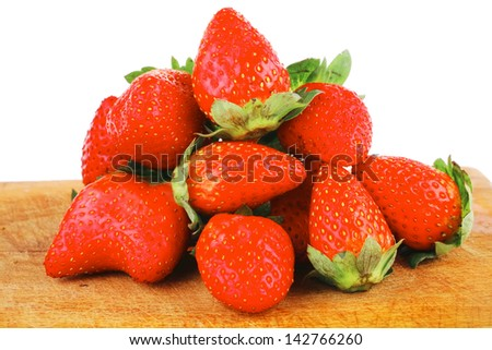 fresh ripe pink strawberry over wooden plate