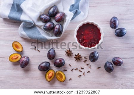 Fresh ripe plums, a white ceramic bowl with homemade plum jam, creasy towel, badyan seeds and dry carnation grains on a wooden table. Flat lay, top view