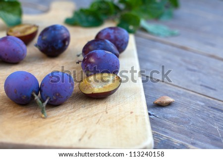 Fresh ripe plums from home garden on wooden cutting board and table in evening light