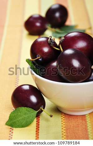 Fresh ripe plums in white bowl. Selective focus, shallow dof