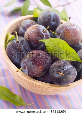 Fresh ripe plums in wooden bowl. Selective focus