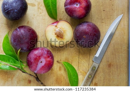 Fresh ripe plums on a chopping board