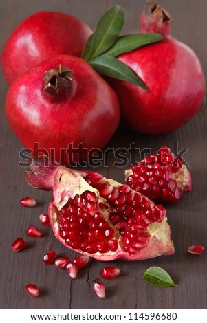 Fresh ripe pomegranates with leaves on an old wooden board.